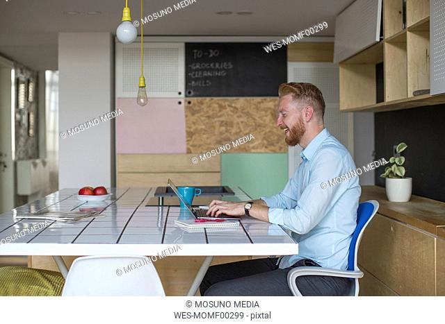 Laughingfreelance businessman working on his laptop at home