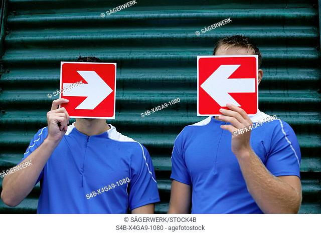 Two men holding arrow signboards in front of the face