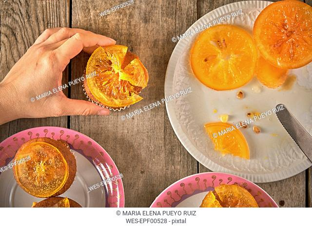 Woman's hand garnishing muffins with candied orange slices