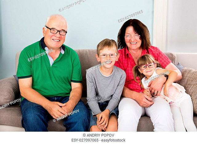 Happy Family Wearing Glasses While Sitting On Couch Together At Home