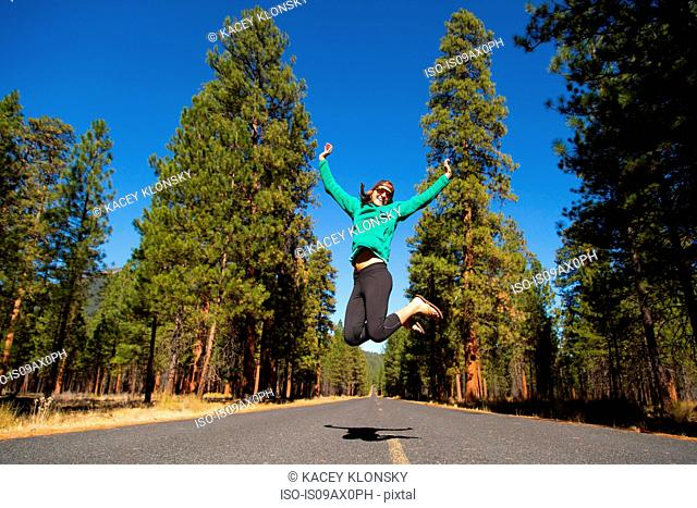 Young woman jumping mid air on forest road, Sisters, Oregon, USA