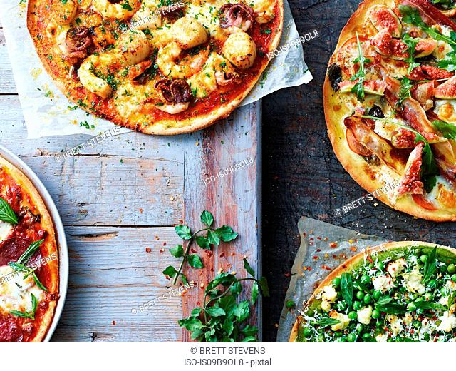 Four fresh pizzas, cropped overhead view
