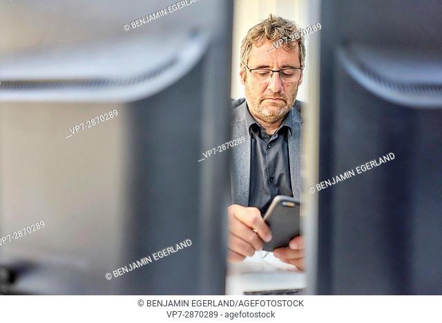 senior business man at work checking smarthpone