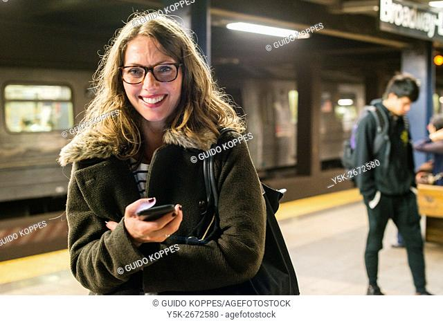 New York City, USA. Blonde, female commuter playing with her smartphone, while waiting for new connecting subway train home bound