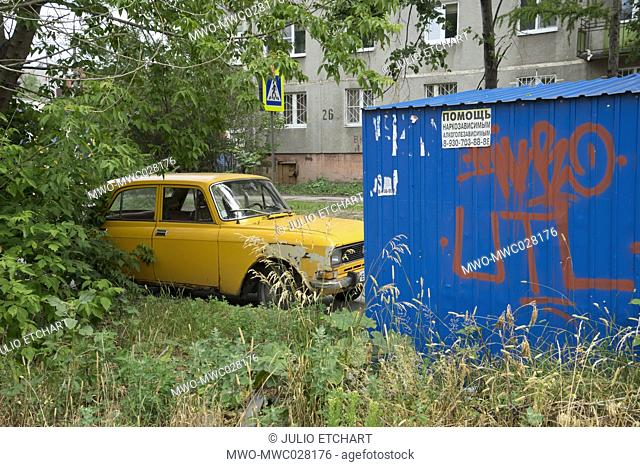 Decaying social housing and old car in a modest neighbourhood of the industrial city of Nizhny Novgorod on the Volga river, Russia