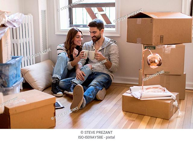 Moving house: Young couple sitting in room full of boxes, drinking hot drink