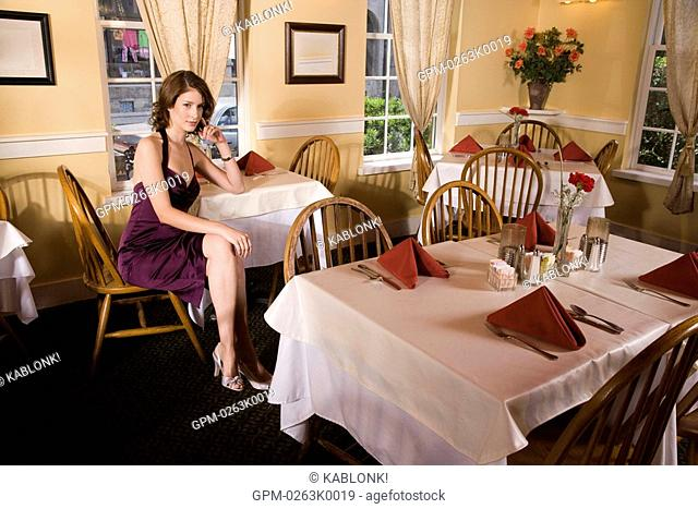 Portrait of mid adult woman waiting alone in restaurant