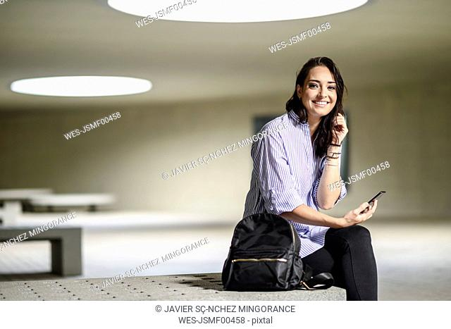 Portrait of smiling student with smartphone and backpack
