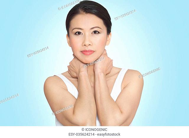 Beautiful fresh natural glowing Asian woman in white top posing over blue background