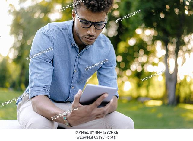 Young man looking at cell phone in park