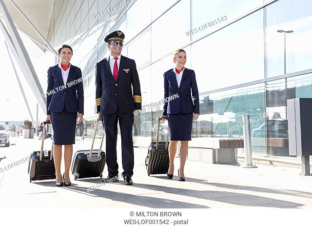 Pilot and stewardesses walking outside airport building