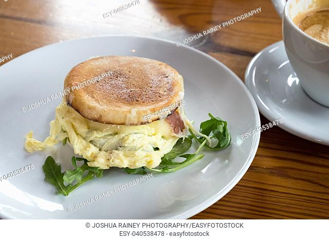 Artisan breakfast sandwich served on an English muffin with cheese, egg, and arugula