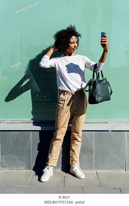 Young casual businesswoman using smartphone in the city, selfie
