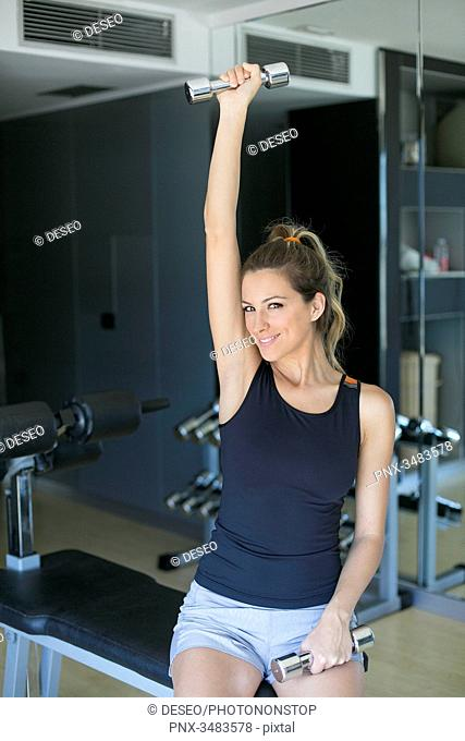 Pretty woman lifting weights in gym