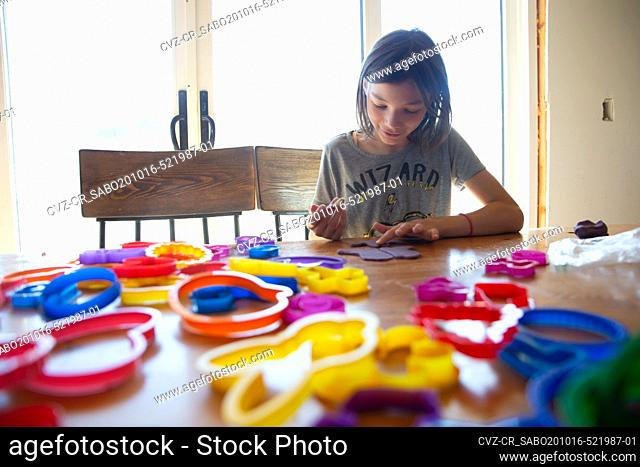 Tween girl making art with clay and cookie cutters