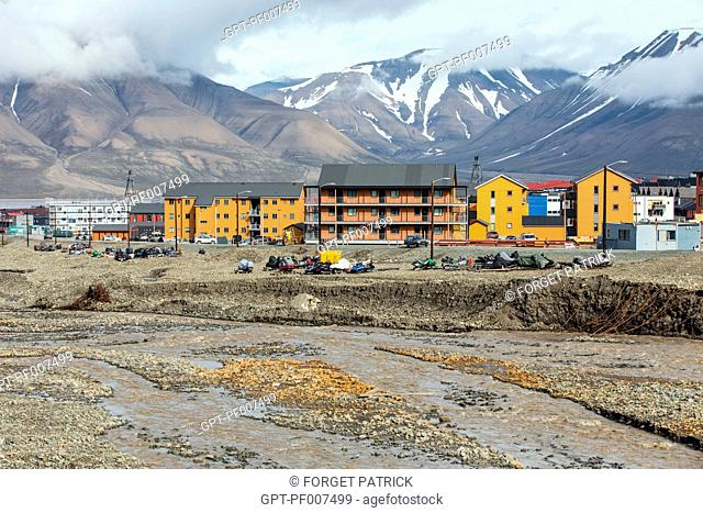 SNOWMOBILE IN FRONT OF THE COLORFUL WOODEN BUILDINGS, CITY OF LONGYEARBYEN, THE NORTHERNMOST CITY ON EARTH, SPITZBERG, SVALBARD, ARCTIC OCEAN, NORWAY