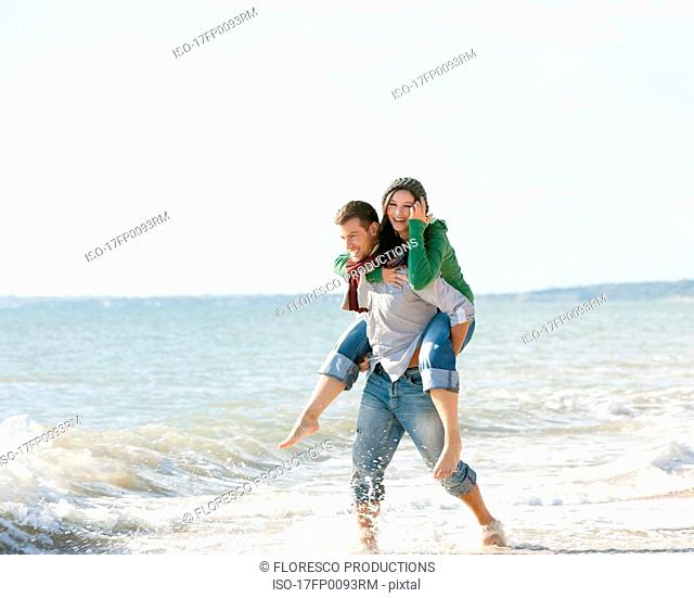 Woman riding piggyback by the sea