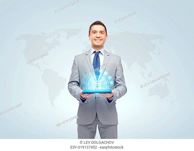 business, trade, people and technology concept - happy smiling businessman in suit holding tablet pc computer with hologram of shopping trolley over world map...