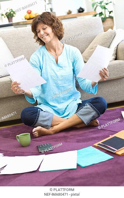 Woman sitting on floor with bills