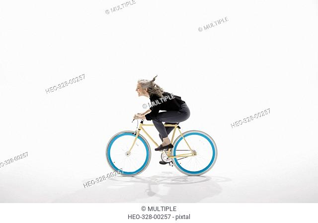 Woman riding bicycle against white background