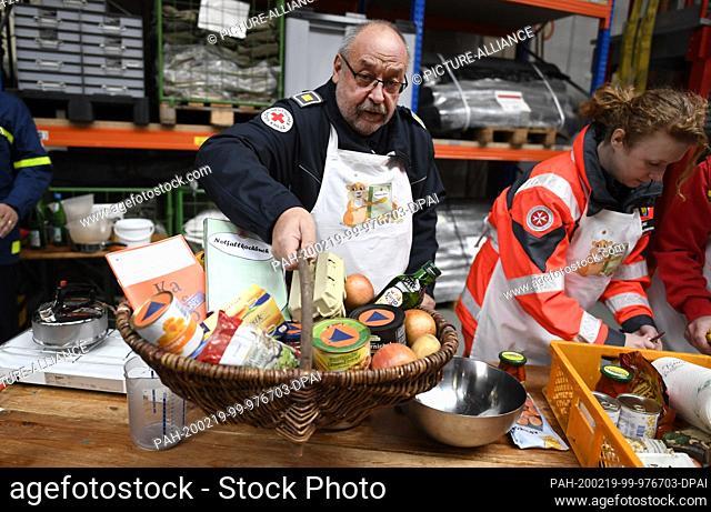19 February 2020, North Rhine-Westphalia, Bonn: Peter Winter, German Red Cross (DRK), lifts a food basket with whose ingredients he will cook