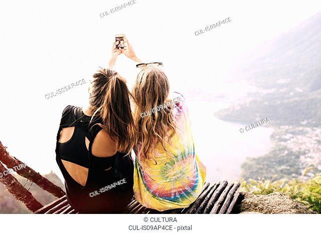 Rear view of two female friends taking smartphone selfie at Lake Atitlan, Guatemala