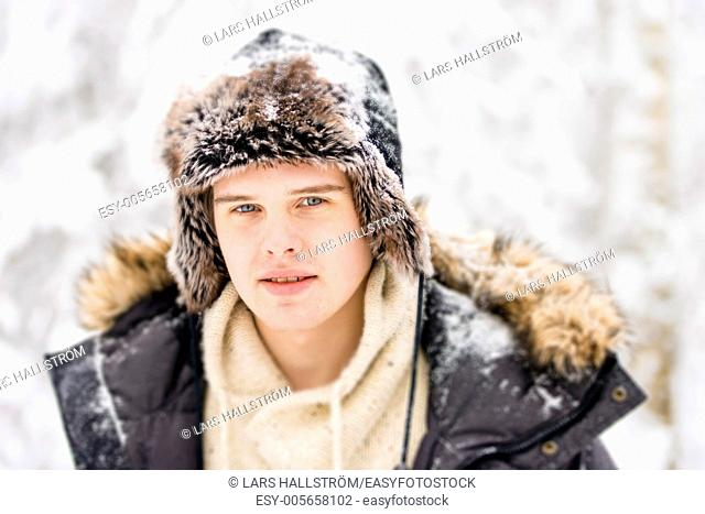 Christmas scene with natural looking teenage male outdoors in snow covered winter landscape