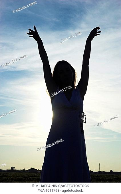 Silhouette of a young woman at dusk, arms raised