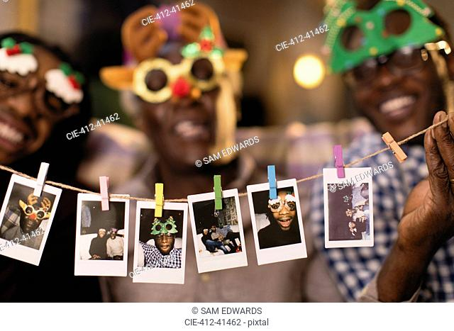 Portrait playful family in Christmas costume goggles showing instant photos