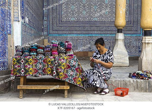 Vigilant who also sells knitwear made by her, in Summer Mosque, inside Kuhna Ark, Khiva, Uzbekistan