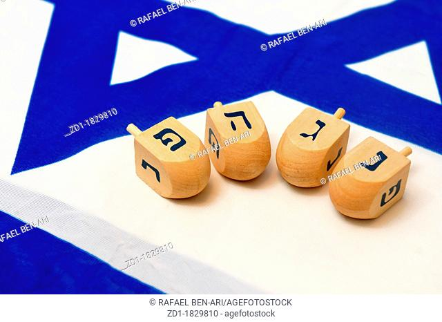 A white and blue Israeli Flag with the star of david on it with wooden dreidels for the Jewish holiday of Hanukkah