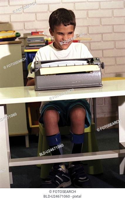 Cute little boy with multiple disabilities, including blindness, using a braille machine as he learns to type a letter