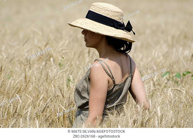 Woman with a straw hat standing in the wheat field in Ticino, Switzerland