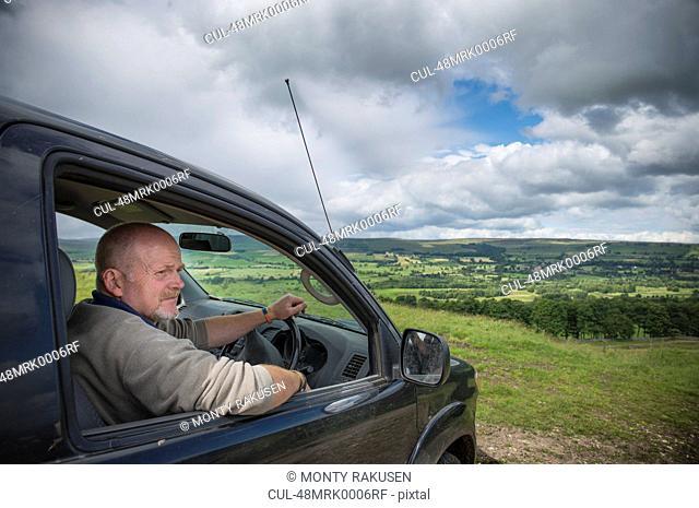Man driving car in rural landscape