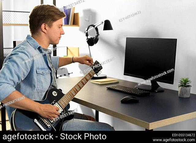young man with computer playing guitar at home