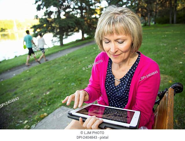 Mature woman using a tablet in a city park; Edmonton, Alberta, Canada