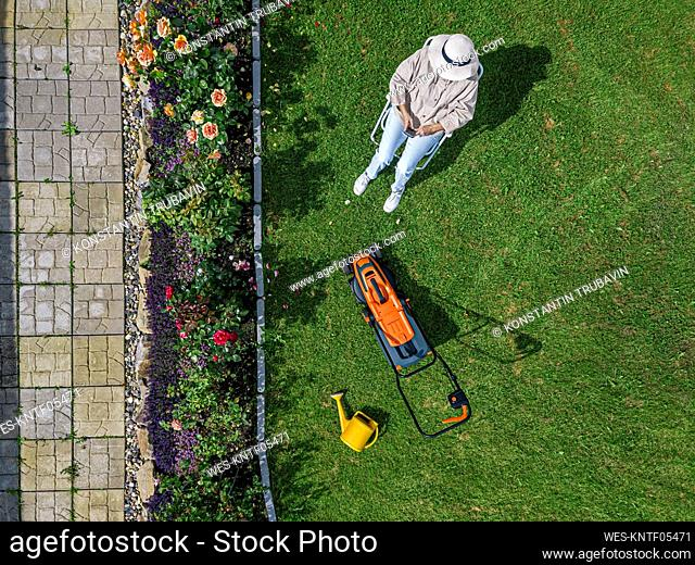 Woman with lawn mower sitting on chair in back yard