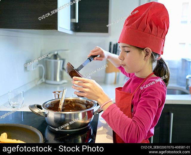 Girl pouring chocolate sauce in cup