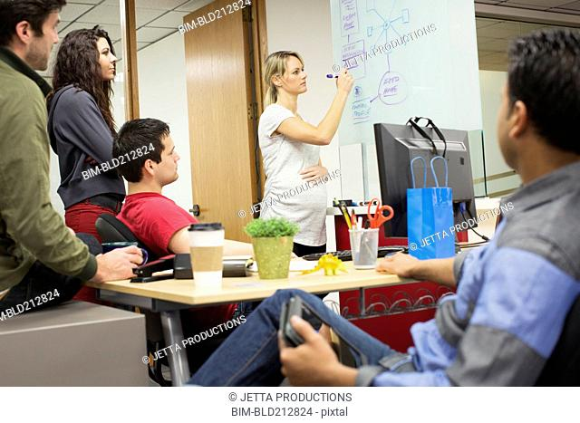 Pregnant businesswoman giving presentation to colleagues in office