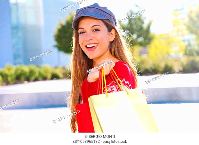 Happy cheerful christmas woman holding shopping bags outdoors