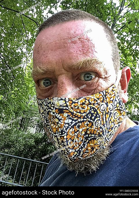 "Berlin, Germany. Sefie of a mature adult male with Corona Haridue wearing a """"protective"""" facemask"