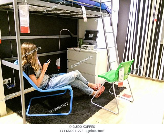 Breda, Netherlands. Young teenage girl buzzy with her smart phone, while sitting in an example teenage room set up at the IKEA store