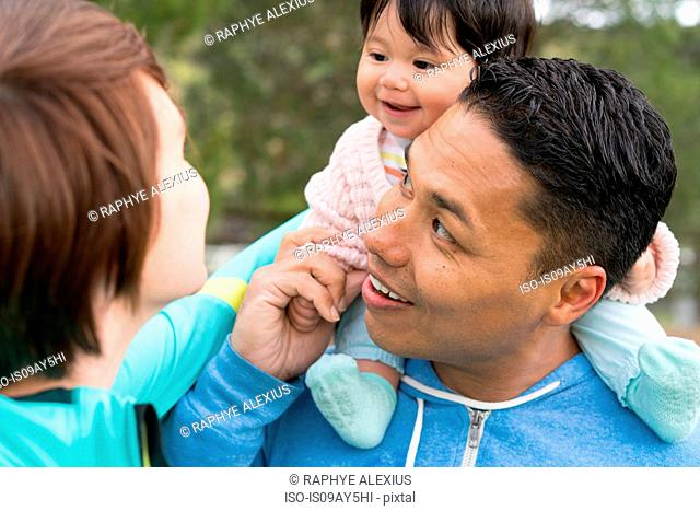 Couple playing piggyback ride with baby in park
