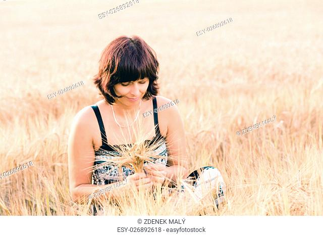 Middle aged beauty woman with summer dress and no makeup relaxing in countryside tearing into bouquet of golden barley with her hand, summer concept