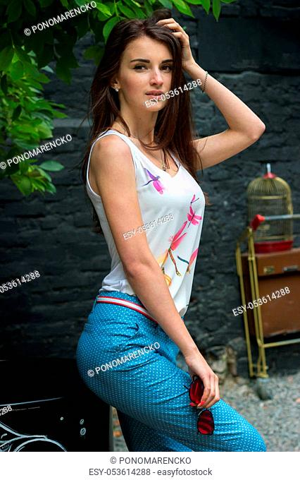 vertical portrait of a young beautiful brunette in jeans and a t-shirt