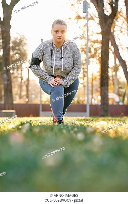 Portrait of curvaceous young woman training in park, leaning forward and crouching