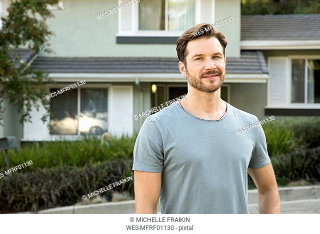 Portrait of confident man in front of his home