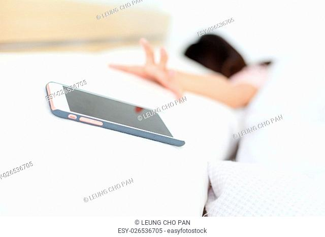 Woman lying on bed and want to get cellphone