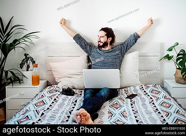 Man stretching while sitting with laptop on bed at home