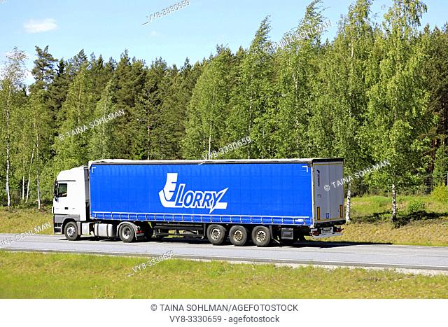 Salo, Finland. May 30, 2019. Side view of white Mercedes-Benz Actros semi truck in front of blue trailer of Lorry JSC at speed on motorway in summer